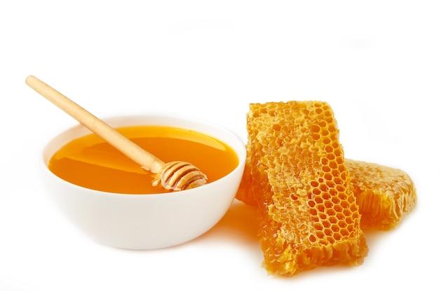 Frischer honig in der schüssel mit wabe lokalisiert auf weiß. draufsicht