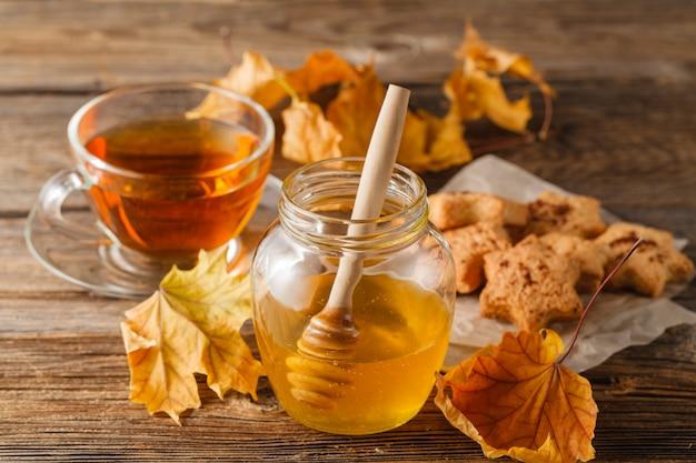 Frischer honig und tasse tee auf einem hölzernen hintergrund