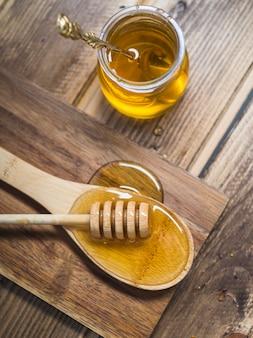 Frischer honigschöpflöffel auf hölzernem löffel und topf mit löffel