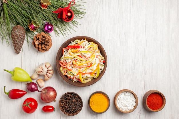 Frischer hühnersalat von oben mit gewürzen auf hellweißem schreibtisch-snack-mahlzeit fleisch frischer salat