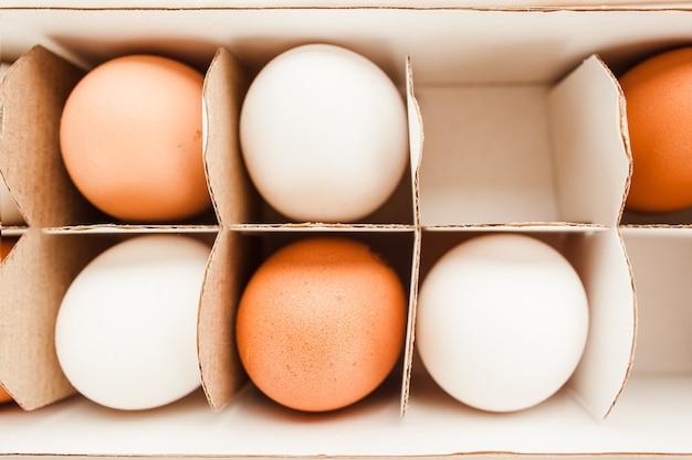 Frischer ingwer und weiße eier verpackt in einer draufsicht des weißen papierbehälters.