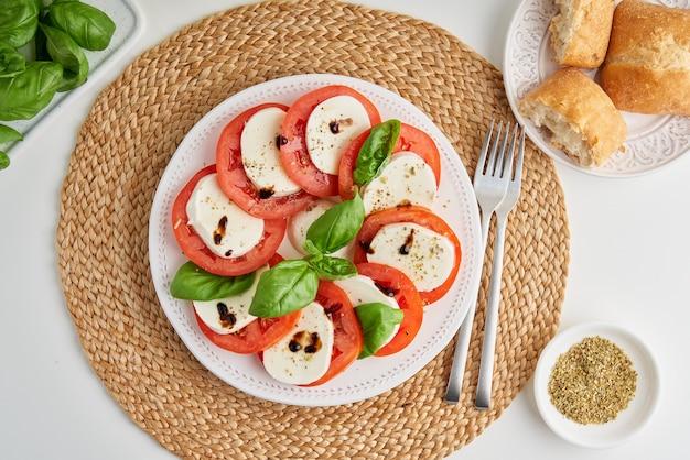 Frischer italienischer caprese-salat mit mozzarella-tomaten-basilikum-olivenöl und ciabatta