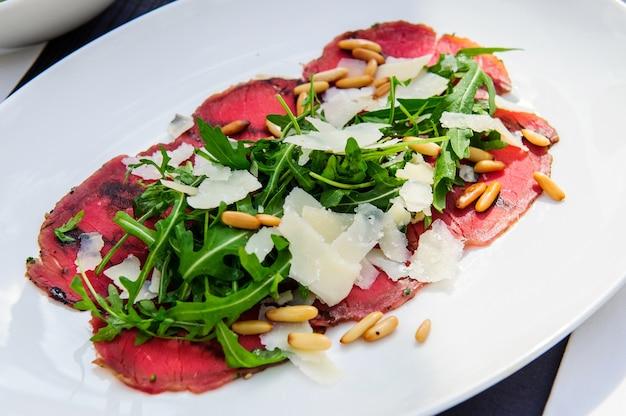 Frischer italienischer caprese-salat mit mozzarella und tomaten auf dunklem teller