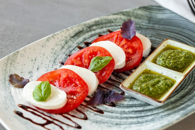 Frischer italienischer caprese-salat mit mozzarella und tomaten auf grauem teller