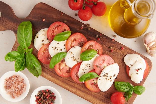 Frischer italienischer salat antipasti namens caprese mit büffelmozzarella, tomatenscheiben und basilikum mit olivenöl. zutaten für vegetarischen caprese-salat. italienisches essen. draufsicht. rustikaler stil.