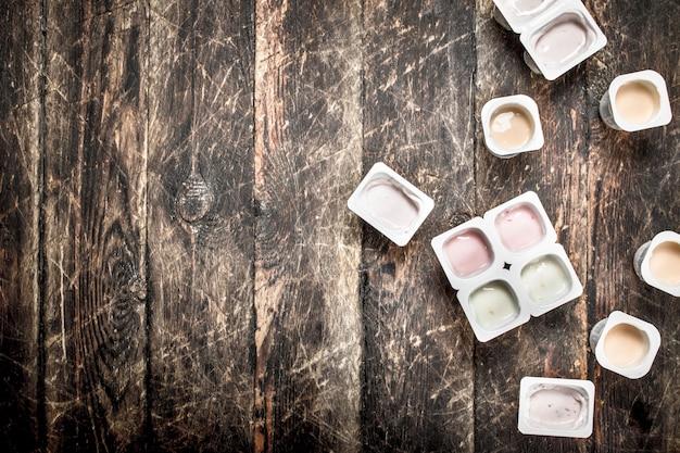 Frischer joghurt aus früchten. auf einem hölzernen hintergrund.