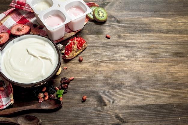 Frischer joghurt mit früchten. auf einem holztisch.