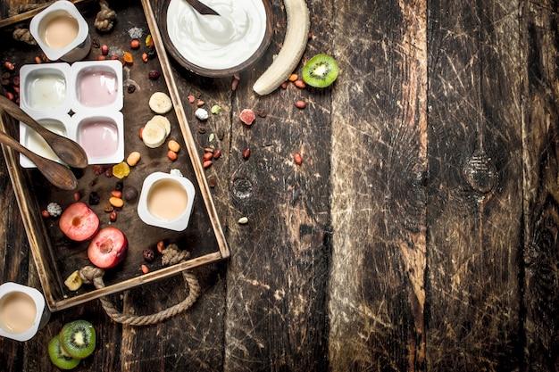 Frischer joghurt mit früchten und nüssen auf einem hölzernen hintergrund