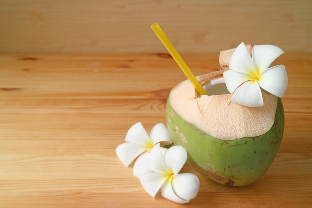 Frischer junger kokosnusssaft mit frangipani-blumen auf einem holztisch