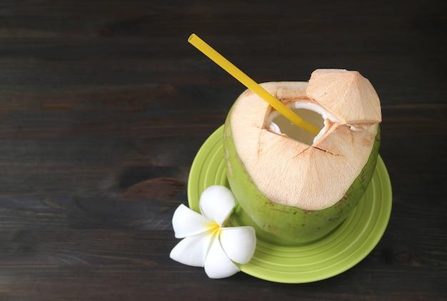 Frischer junger kokossaft mit einer frangipani-blume auf schwarzem holztisch