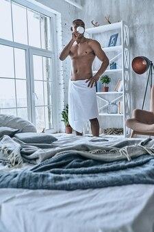 Frischer kaffee. hübscher junger afrikanischer mann bedeckt mit duschtuch, der kaffee trinkt