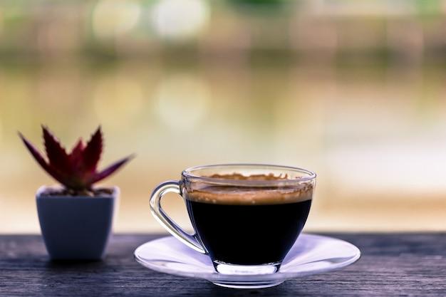 Frischer kaffee im klarglas gesetzt auf einen holztisch, kopienraum.