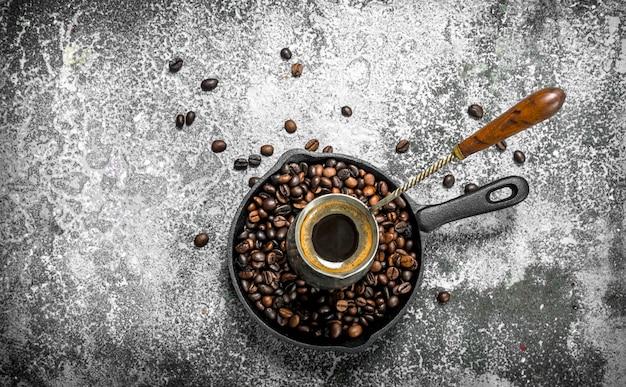 Frischer kaffee im türken. auf einem rustikalen hintergrund.
