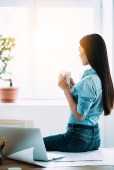 Frischer kaffee macht ihren tag. rückansicht der jungen asiatin mit kaffeetasse