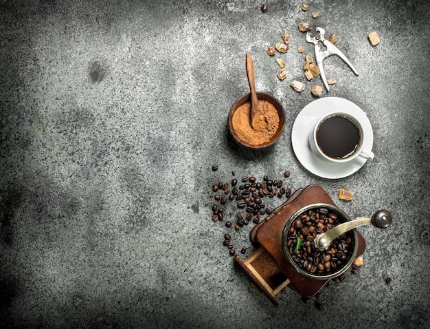 Frischer kaffee mit in einer tasse mit einer kaffeemühle. auf einem rustikalen hintergrund.