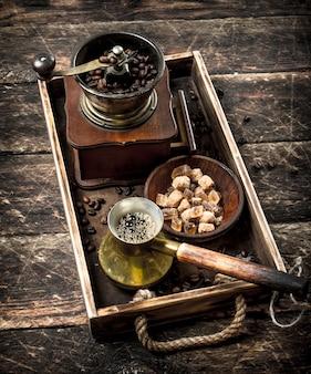 Frischer kaffee mit zucker und kaffeebohnen auf einem alten tablett. auf einem holztisch.