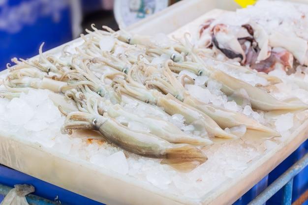 Frischer kalmar auf eisverkauf am stall im großen seehafen des mahachai-straßenmarktes des meeresfrüchtemarktes in thailand