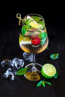 Frischer kalter cocktail mit limette und kirsche auf schwarzem hintergrund