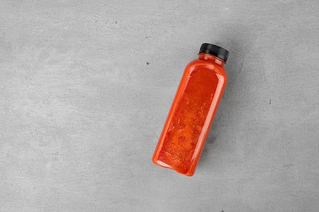 Frischer karottensaft in plastikflasche auf grauem hintergrund