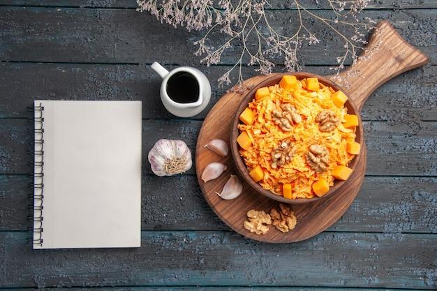 Frischer karottensalat von oben mit knoblauch und walnüssen auf dunkelblauer schreibtisch-nuss-diät-gesundheitssalatfarbe