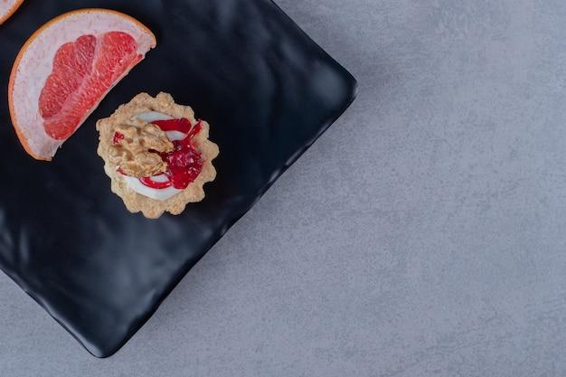 Frischer keks mit grapefruitscheibe auf schwarzem teller