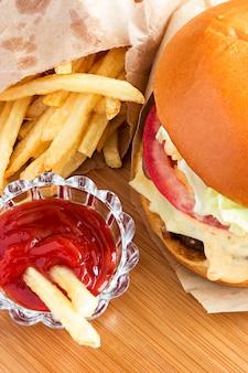 Frischer klassischer burger mit pommes-frites und soßenketschup auf hölzernem hintergrund