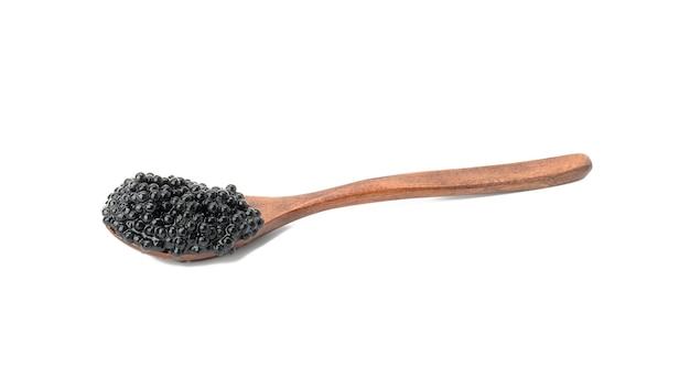 Frischer körniger schwarzer paddelfischkaviar in braunem holzlöffel auf weißem hintergrund, nahaufnahme