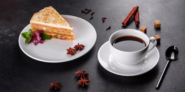 Frischer köstlicher karottenkuchen mit sahne auf einer dunklen oberfläche. karottenkuchen mit geschlagenem zuckerguss
