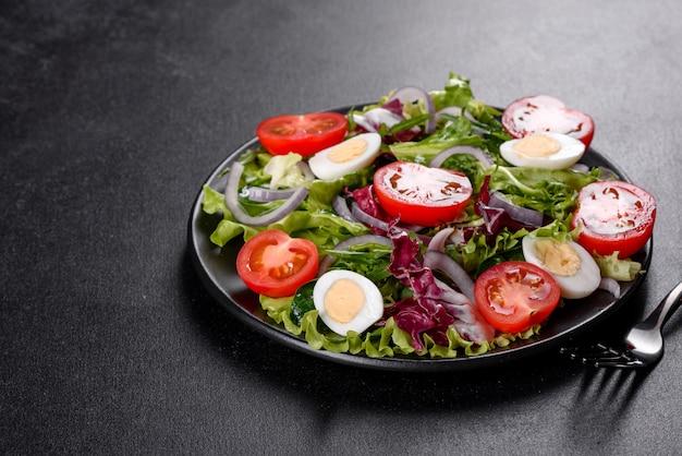 Frischer köstlicher vegetarischer salat des gehackten gemüses auf einem teller auf einem dunklen betonhintergrund