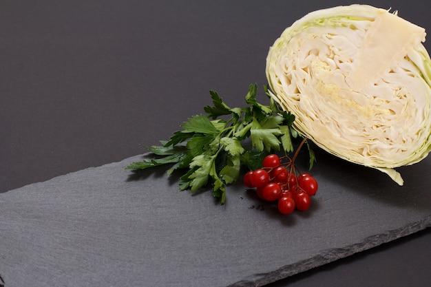 Frischer kohlkopf und viburnum-cluster im hintergrund. veganer salat. das gericht ist reich an vitamin u. nahrung für eine gute gesundheit.