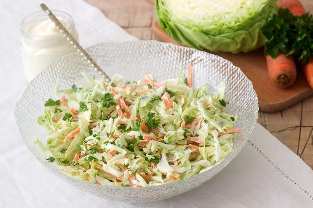 Frischer kohlsalatsalat in der schüssel und in den bestandteilen für salat. rustikaler stil.