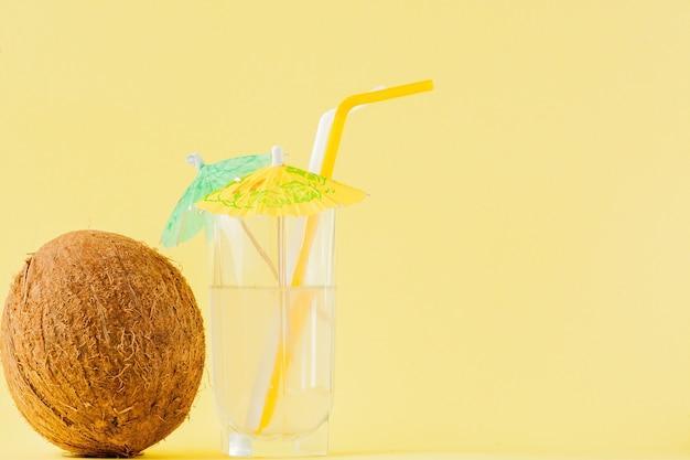 Frischer kokoscocktail mit strohhalmen an gelber wand, kopierraum.