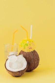 Frischer kokoscocktail mit strohhalmen auf gelber wand.