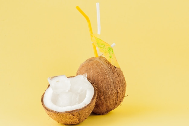 Frischer kokosnusscocktail mit einem strohhalm auf gelbem hintergrund, kopienraum