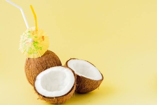 Frischer kokosnusscocktail mit einem strohhalm auf gelbem hintergrund, kopienraum.