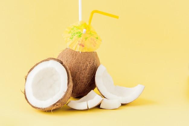 Frischer kokosnusscocktail mit einem strohhalm auf gelber wand, kopienraum.