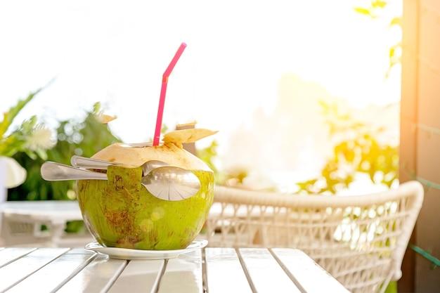 Frischer kokossaft mit strohhalm und zwei löffeln auf weißem holztisch gegen verschwommenen strand und berg
