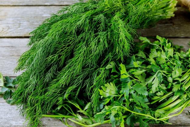 Frischer kräuterdill, petersilie, spinat, minze, wilder knoblauch auf einem hölzernen hintergrund. op-ansicht. platz kopieren.