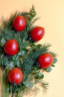 Frischer kräuterdill, petersilie, tomate am gelben papierhintergrund