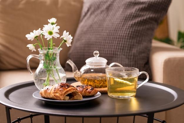 Frischer kräutertee in tasse und teekanne, hausgemachtes croissant auf teller und glaskrug mit weißen blumen auf kleinem tisch gegen kissen auf sessel