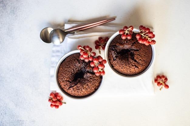 Frischer kuchen schokoladenfondantkuchen mit roten shepherdia argentea beeren serviert in einer schüssel