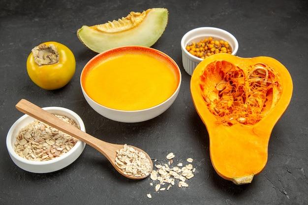 Frischer kürbis der vorderansicht mit kürbissuppe auf einer dunkelgrauen tischsuppe färbt fruchtreife