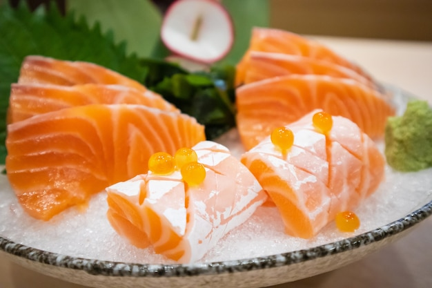 Frischer lachsscheiben-sashimi auf eis nach japanischer wasabi-art servieren