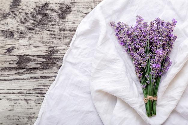 Frischer lavendelblumenstrauß auf altem rustikalem holztisch auf stoff. flatlay lila kräuterblüte. blumenstrauß aus lavendel mit kopienraum für text. lavendel aromatherapie. lavendelblüten trocknen.
