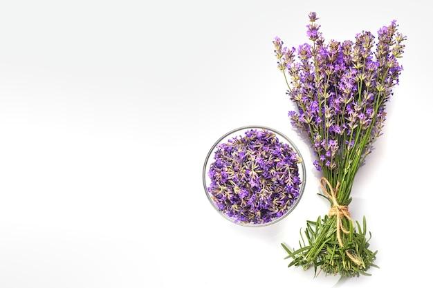 Frischer lavendelstrauß und lavendelblüten in glasschale