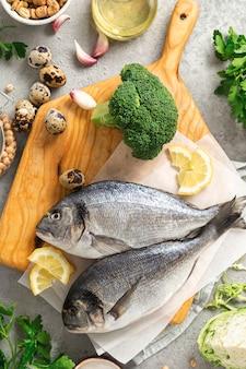 Frischer lebensmittelhintergrund rohe kochzutaten für leckeres und gesundes essen. draufsicht auf frischen fisch, gemüse, kräuter und hülsenfrüchte