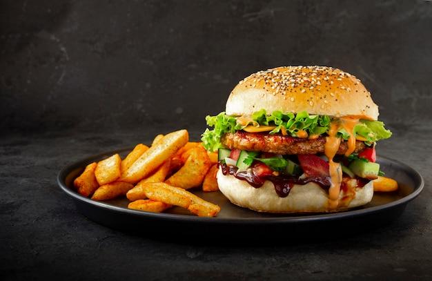 Frischer leckerer chicken burger mit pommes frites auf dunklem hintergrund