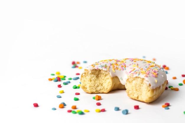 Frischer leckerer donut und süße mehrfarbige dekorative süßigkeiten auf weißem hintergrund. bäckereikonzept, frisches gebäck, leckeres frühstück.