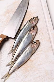 Frischer leckerer fisch auf schneidebrett mit einem messer
