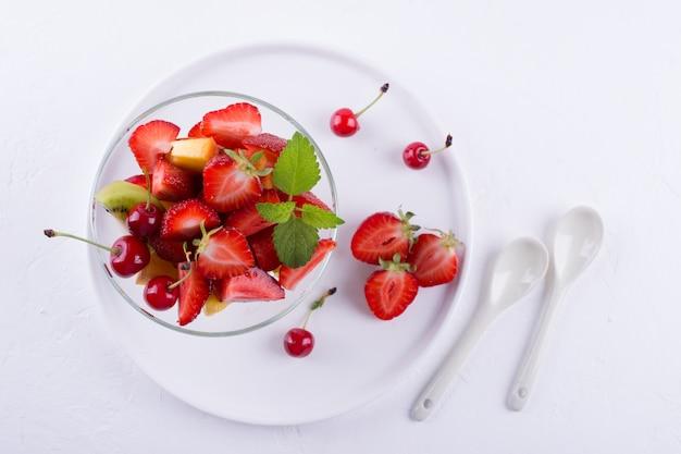 Frischer leckerer mischfruchtsalat in der glasschale auf weißem tischhintergrund. gesundes vitaminfrühstück draufsicht